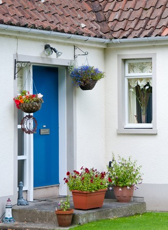 Cottage house exterior with flowers in the backyard Stock Photo