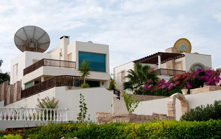 architecture bungalow: Group of luxury holiday villa houses with nice garden and satellite dishes on the roof.  Editorial