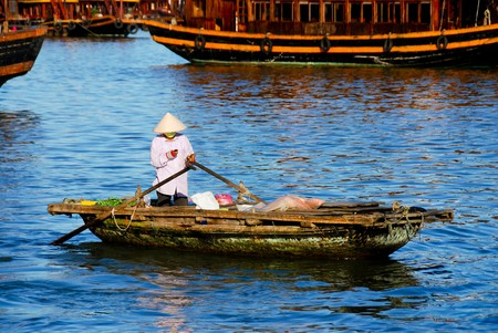 Vietnamese woman selling vegetables and fruits to tourists from the wooden boat