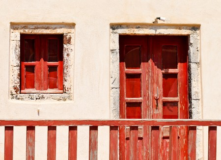 Exterior of an abandoned house with red window and door in Santorini island, Greece photo
