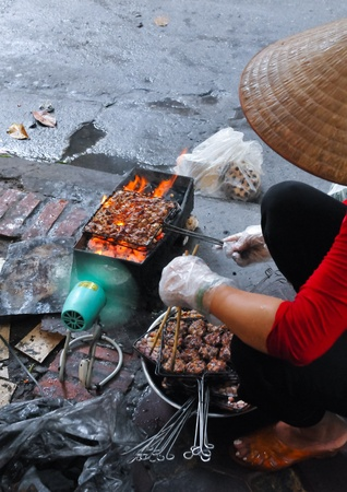 Woman is doing barbeque on grill, at the streets of Hanoi in Vietnam