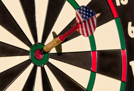 Dart board with the arrow in center.  photo