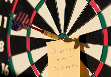 Dartboard with the arrow in center and a note creating a business concept. photo