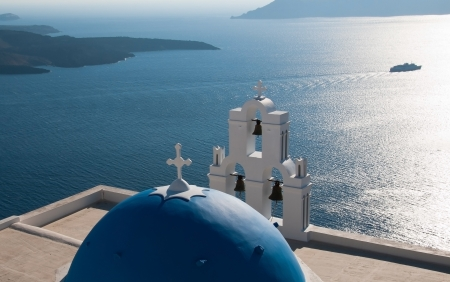 Famous blue domed church in Santorini island  in Greece  facing the caldera photo