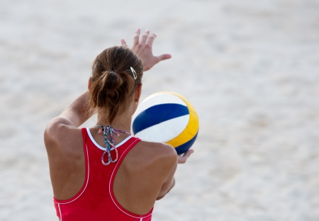 Young unrecognizable athlete ready to serve on a beach volley  game  photo