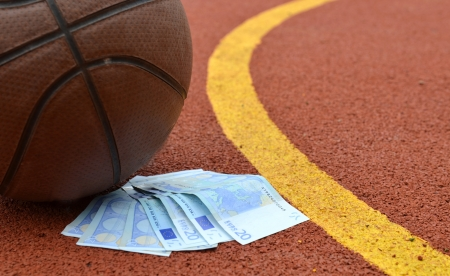 Basketball and euro money on a court  Concept for sports econom photo