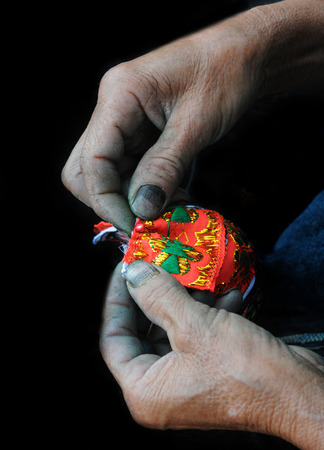 Old Woman knitting a small red wallet. Vietnam, Asia. photo