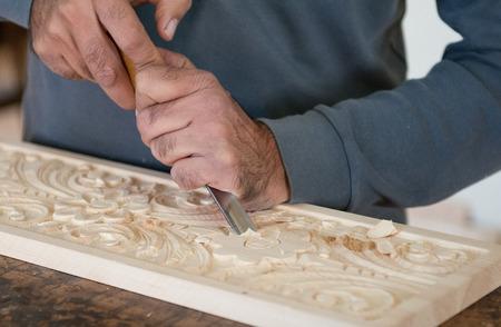 Man scultore scolpire il legno per creare un disegno flora legno