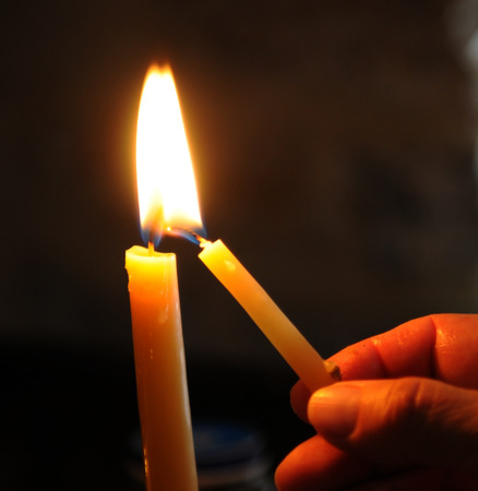 churches: Human hand holding and lighting the candle in church for pray and make a wish. Stock Photo