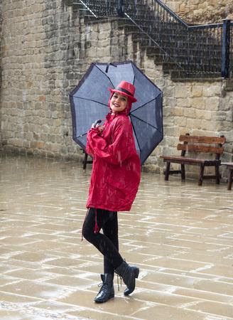 Jonge gelukkige mooie vrouw die zich in de regen Stockfoto