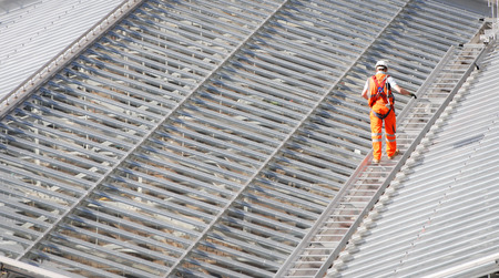 Male Worker wearing an orange suit walking on the top of a steel roof structure of a railway station Stock Photo