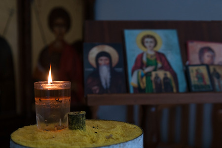 iconography: Candle light illuminating in front of orthodox saint pictures. Symbol of religion and faith. Stock Photo