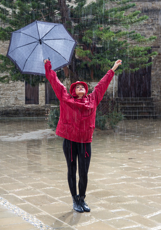 Young  beautiful caucasian woman with an umbrella dressed in Red and  dancing in the rain. photo