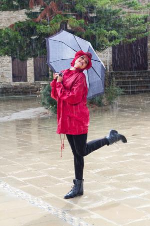 Jonge mooie blanke vrouw met een paraplu gekleed in rood en dansen in de regen. Stockfoto
