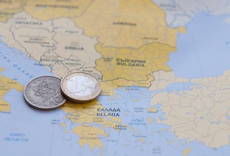 european map: Euro coin and drachma on a European map. Concept of Europe financial Crisis.
