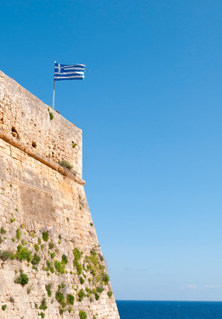fortezza: Greek flag waving  on  Rethymno  Venetian fortezza, citadel, in Crete Greece. Clear blue sky and ocean at the  background. Editorial
