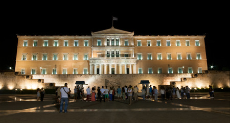 evzone: Athens, Greece - August 28, 2014: Tourists in front of the tomb of the unknown soldier in the  parliament building of  Athens, watching the change of the evzone guards