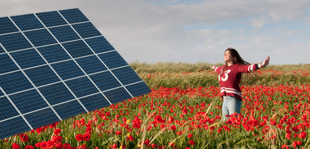flower power: Solar power energy panel on a field with red poppy flowers and a teenage girl jumping happy with joy for saving the environment.  Concept of renewable energy sources. Stock Photo