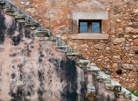 Abstract of a Simple Brown stone wall with a small closed window and stairs photo