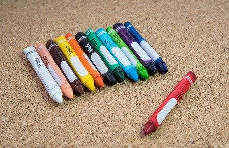 brown cork: Colored  drawing crayons on a brown cork board Stock Photo