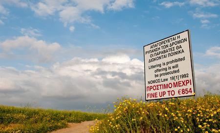 botar basura: Se�al de peligro para prohibir tirar basura de la basura de ning�n tipo sobre los campos. Advertencia est� en lengua griega e Ingl�s Foto de archivo