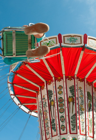 turnabout: Colorful merry-go-round carousel with unrecognized  person sitting on the chair and spinning around