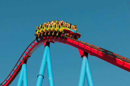 Young  People on a Rollercoaster Ride in famous Port Aventura  amusement park against a blue sky in Barcelona, Spain