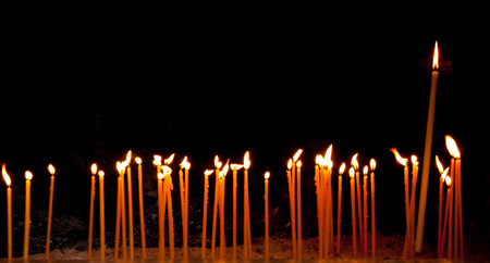 Group of religious candles burning in a orthodox christian church for prayers and wishes.