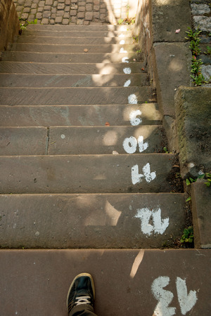 concrete steps: Concrete steps with step numbers remaining to reach the bottom. Stock Photo