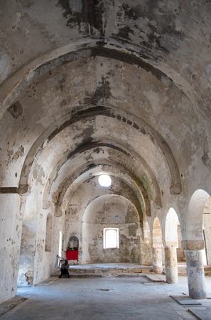 panteleimon: Interior of the abandoned orthodox monastery  of Saint Panteleimon at the village of Myrtou in Cyprus with an unrecognized person praying