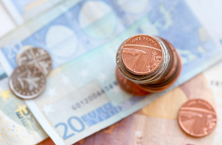 20 euro: One british penny coin on a pile  and  20 Euro  note