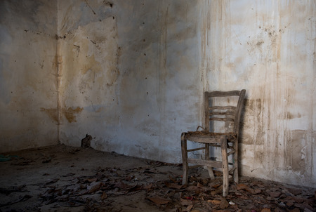 dirty room: Interior of an abandoned spooky empty room with white dirty wall and a wooden chair. Concept of abandonees and desolation