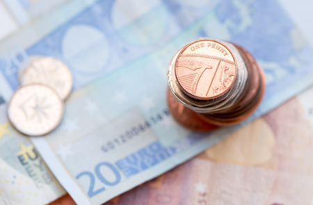 20 euro: British one penny coin on a pile of coins and 20 Euro note Stock Photo