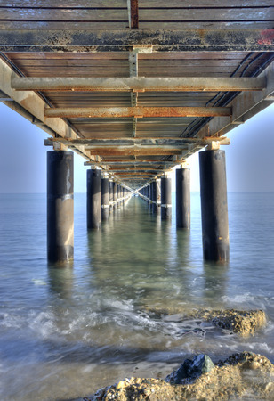 directive: Rusty metallic  pier from sea level in vertical composition creating a diagonal directive tunnel.