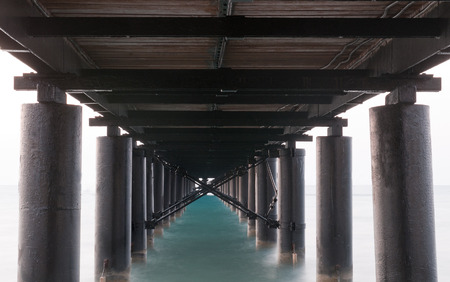 directive: Rusty metallic  pier from sea level in horizontal composition creating a diagonal directive tunnel.