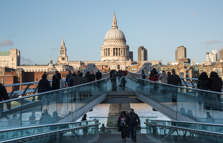millennium: People walking at the  Millennium bridge , officially known as the London Millennium Footbridge crossing river Thames Saint Paul Cathedral at a distance.