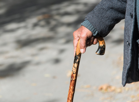 wooden stick: Senior man holding a traditional  wooden stick to provide support and help him  walk safely