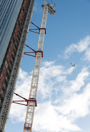 construction platform: Construction of a modern skyscraper building with a construction platform and a crane on a cloudy day Stock Photo