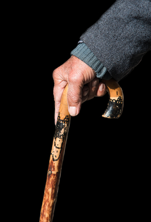 Senior man holding a traditional  wooden walking stick isolated on a black background. Stick is used to provide support and help him  walk safely