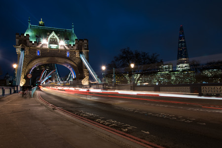 light traces: London tower Bridge, UK, at night with cars and buses leaving colorful light traces.