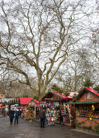hyde: Christmas market with small shops selling Christmas gifts and people around at Winter wonderland in Hyde Park in London UK