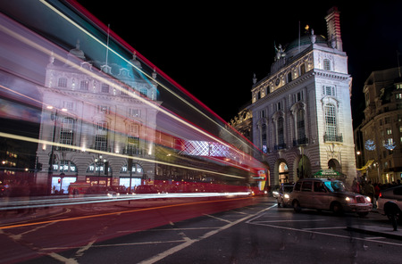 piccadilly: Night scene from the famous London Piccadilly circus square  at the center of London with cars and buses leaving colorful light traces.