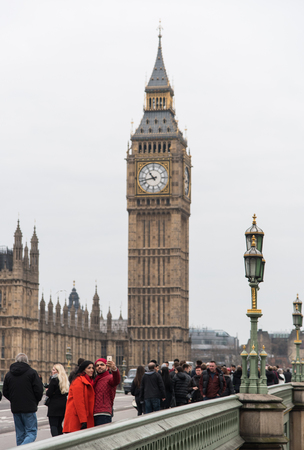 westminster city: London, England - December 14, 2015: People walking on the Westminster Bridge  in London city near famous Westminster and Big ben clock landmarks of London .
