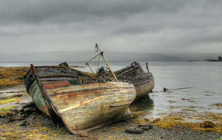 Abandoned wooden fishing boats in the coast of the Isle of Mull in Scotland. Stock Photo