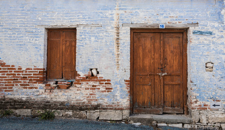 stoned: Exterior of an old village house with blue stoned wall and closed vitnage door and window. Stock Photo