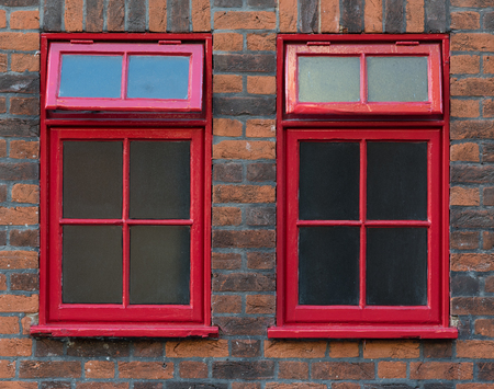 red metallic: Traditional Red metallic  English closed windows on a bricked wall Stock Photo
