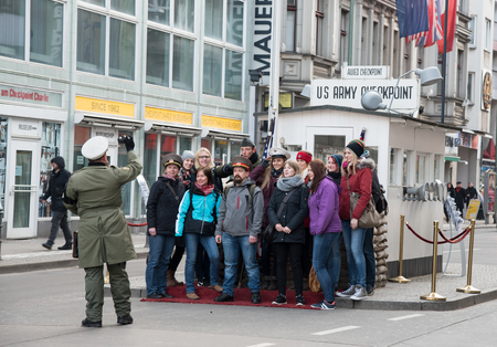 east berlin: Berlin, Germany - January 17, 2016: Group of  Tourists taking photos with guards at famous Checkpoint Charlie crossing point between East Berlin and West Berlin.