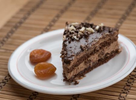 frutas secas: Rebanada de pastel de chocolate con guarnici�n de frutos secos en un plato con frutas secas.