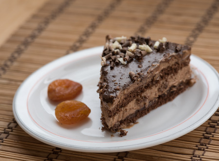 frutas secas: Slice of chocolate cake  garnished with nuts on a plate with dry fruits.