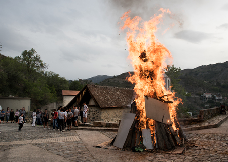 effigy: Palaichori, Cyprus - May 2 2016: People outside a church with fire burning (lampratzia)  Judas Iscariot effigy who betray Jesus Christ  for Easter Celepbration at the village of Palaichori in Cyprus